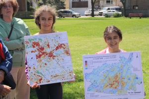 Nicole and Nathalie hold up maps showing heat concentration on Island of Montreal.  Cote Saint-Luc is a hot spot making preservation of Meadowbrook even more important.