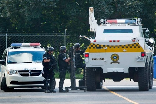 Members of the Montreal police tactical team keep watch on a house in Montreal, Tuesday, July 30, 2013, during a standoff with an armed man believed to be barricaded in his home. (Photo: Canadian Press)