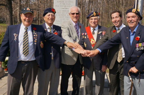 Veterans and members of the Frederick Kisch Branch 97 of the Royal Canadian Legion before the cenotaph in Veterans Park