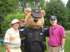 Police mascot Flick with his trusty sidekick Sargent Bryan Cunningham conduct a golfers ID check on George and Glenn J. Nashen