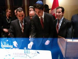 Prime Minister Justin Trudeau lights the Chanukah Menorah in Parliament as MPs Michael Levitt and Anthony Housefather look on