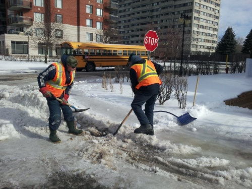 Public Works crews clear the catch basin of ice and snow so water can drain away